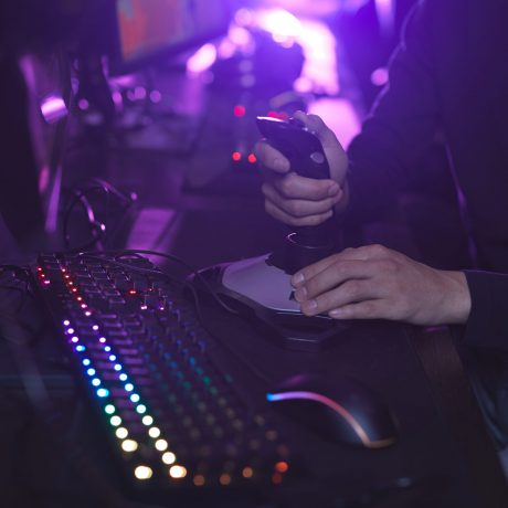 Close up of unrecognizable man using racing joystick while playing video games in dark room, copy space